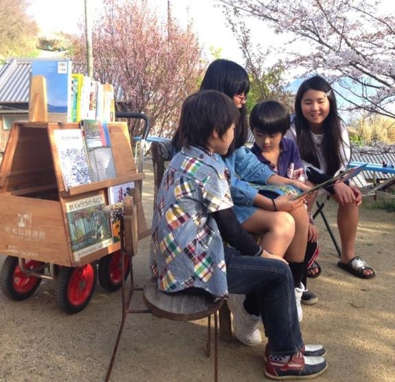 """男木島のアーティスト、「オンバファクトリー」制作の手押し車""""オンバ""""に本を載せて。桜の下、夢中で本を読む子どもたち"""